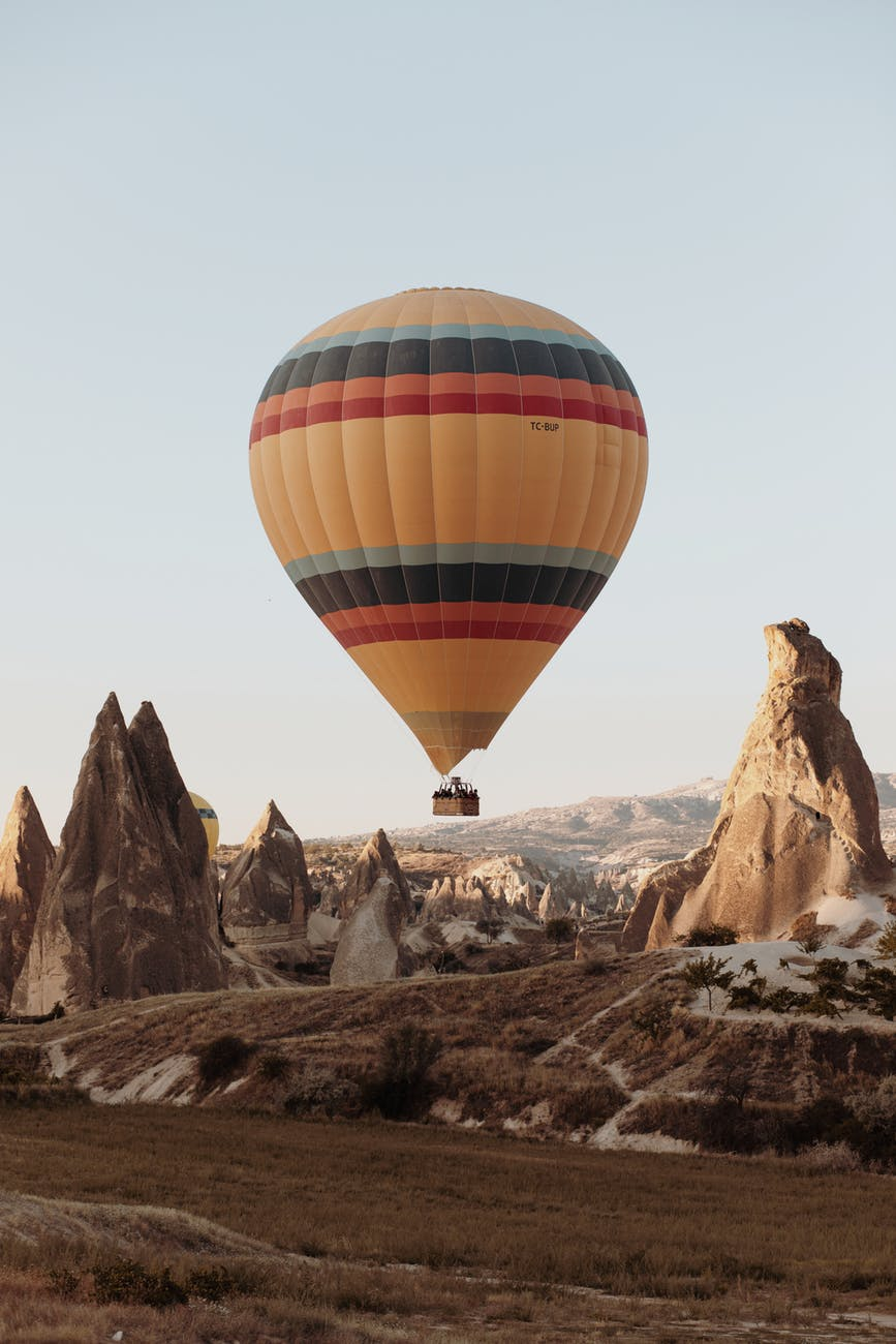 hot air balloon on mid air above rock formation